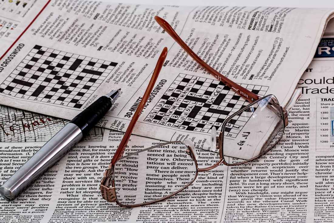 Crossword puzzle, pen and eyeglasses
